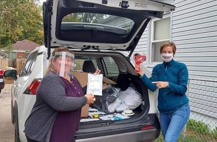 Two women, one wearing a clear face mask and the other wearing a clear face shield, smile at the camera while loading supplies into a car.