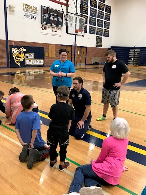John Kusku kneels on a basketball court while talking to three children about goalball.
