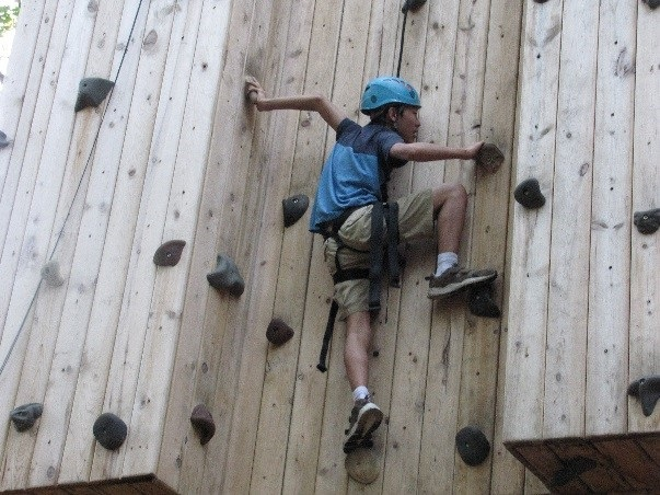A student wearing a blue helmet and climbing gear climbs up a wooden rock wall at Camp Tuhsmeheta.