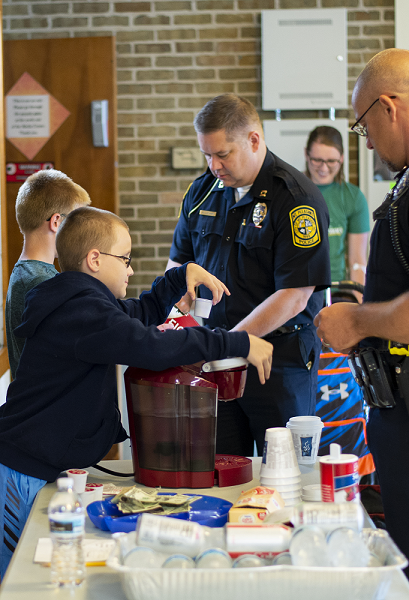 A young boy places a coffee pod into a single-serve coffeemaker as two male police officers watch.