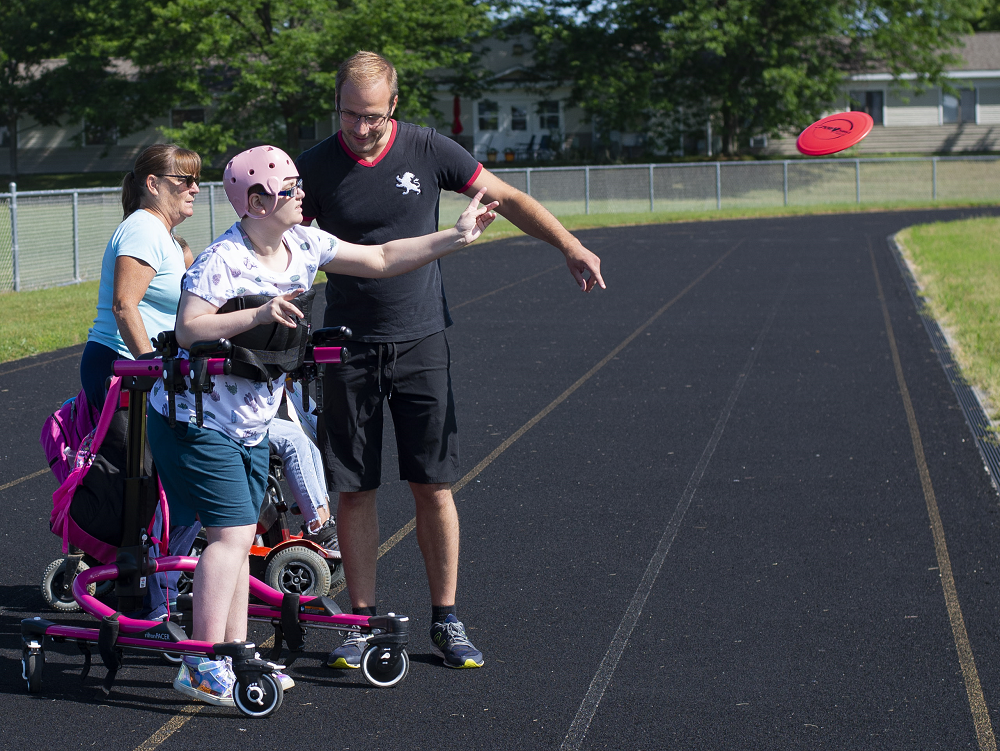 A teen girl wearing a pink helmet throws a small disc as two adults stand next to her.