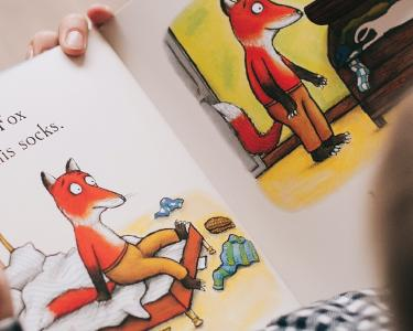 View from above of a young child who is looking at an illustrated book about a fox.