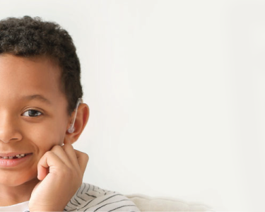 A young boy wearing a hearing device smiles at the camera while sitting on a couch.