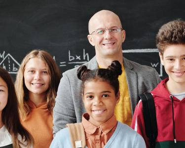A teacher smiles while posing for a photo with several teens in front of a chalkboard.