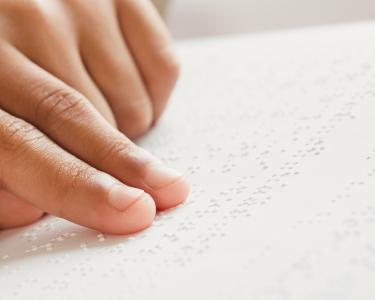 Closeup of a child's hands reading a book in braille.