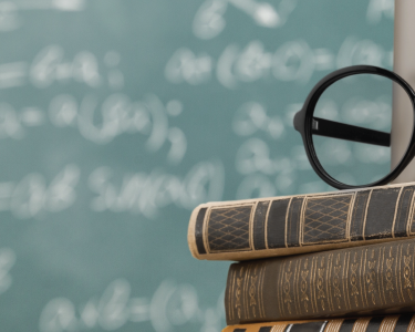A mug and reading glasses rest on top of a stack of books in front of a chalkboard.