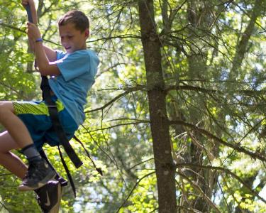 A boy smiles while rappelling down from a wooden climbing wall in the woods.