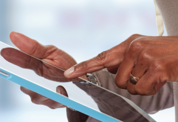 Closeup of a woman's pointer finger poised to touch a tablet device.