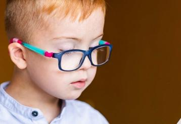 A young boy wearing glasses with a multicolored frame looks down at a book.