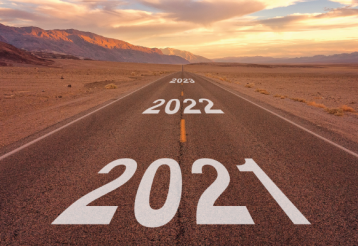 A straight two-way road stretching out into the distance in a desert; the years 2021, 2022, and 2023 are printed on the road.