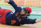 Goalball player John Kusku, wearing an eye cover, slides sideways and stretches his arm out to block a goal.