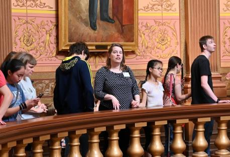 Several adults and children stand next to a large circular railing as a tour guide describes features of the Lansing capitol building.
