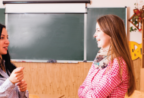 Two women smile as they talk in a classroom with bright colors and plants.