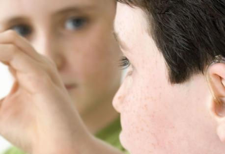 View from behind a young boy who is wearing a hearing device. Another young boy in front of him signs the letter