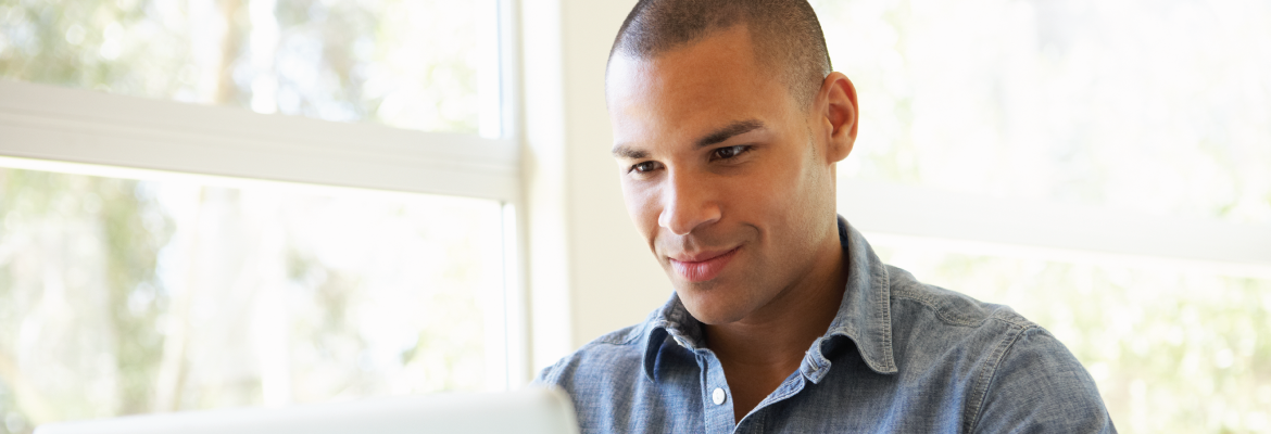 Closeup of a man smiling at a laptop while sitting next to a large window.