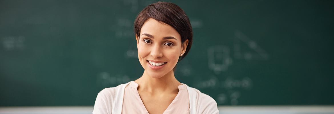 A young woman standing in front of a chalkboard