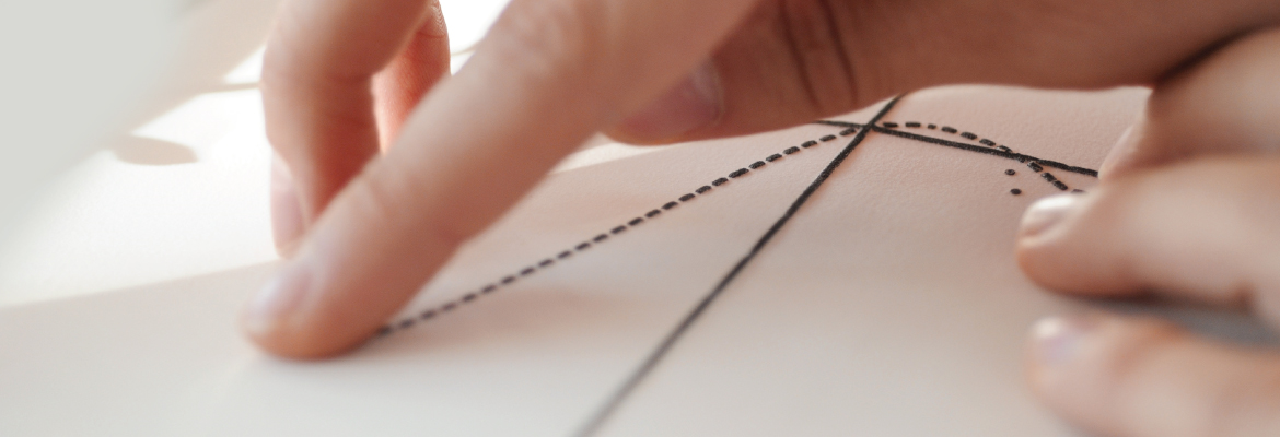 Closeup of fingers touching a raised tactile graph on white paper.