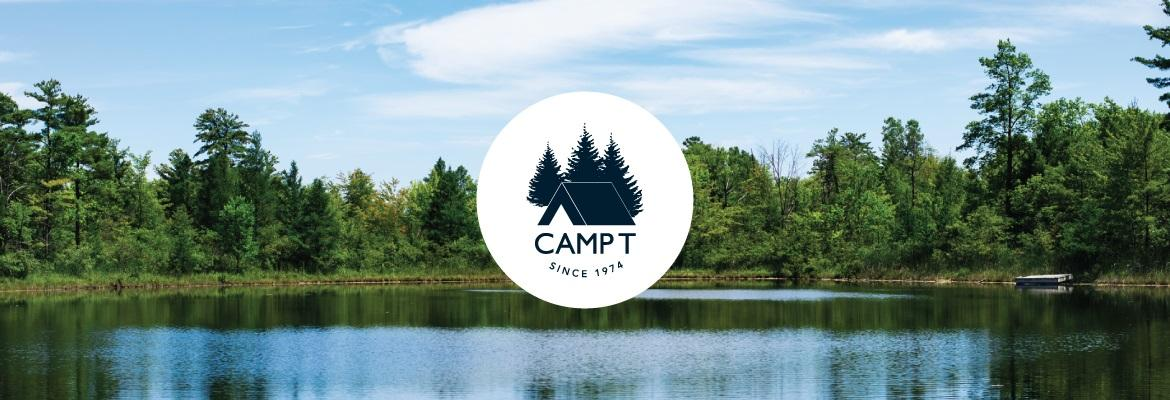 A small tree-lined lake on a sunny summer day with the Camp T logo overlaid in the middle.
