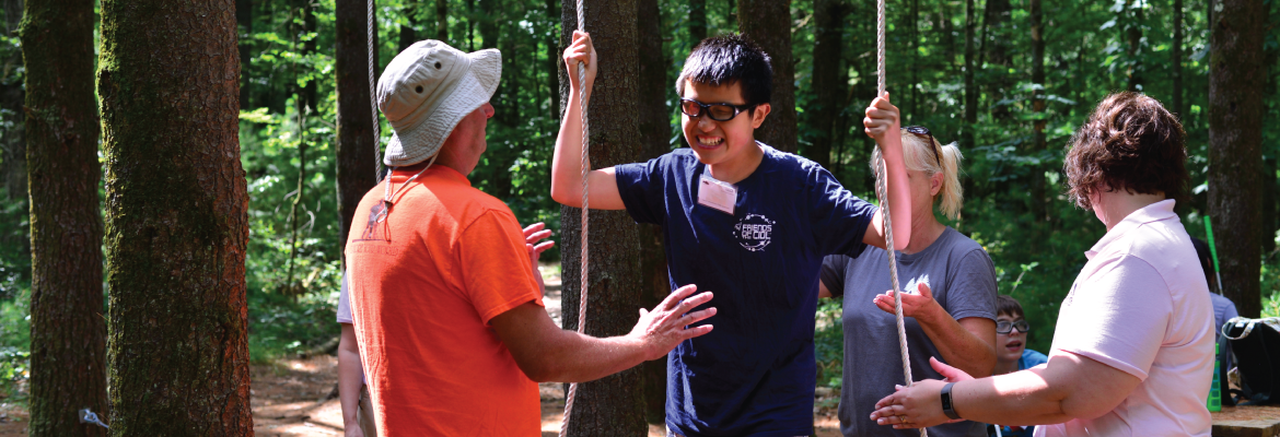 A teenager wearing glasses smiles as he holds two vertical ropes in an outdoor setting.