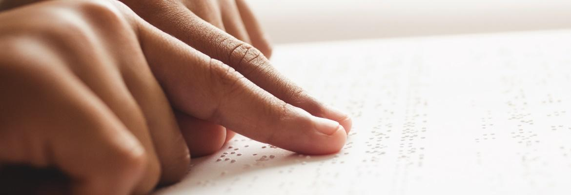 Closeup of a person's hands reading a line of braille.
