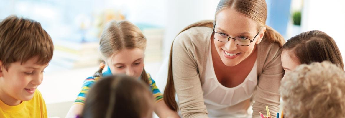 A female teacher wearing glasses leans over and smiles at a child who is seated with four other children at a table.