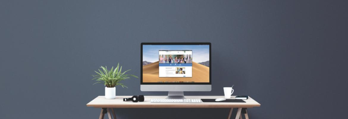A desk with a computer displaying the MDE-LIO website