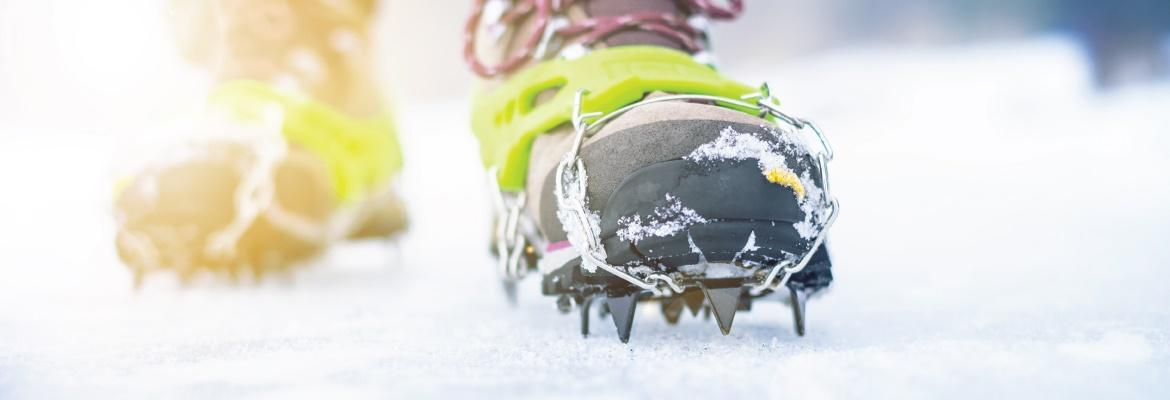 Closeup of a person's boots with ice cleats in the snow.