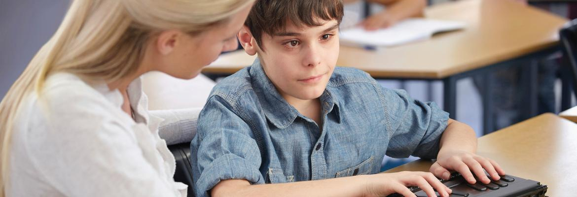 A teacher sits at a desk next to a boy who is using a small rectangular assistive technology device.