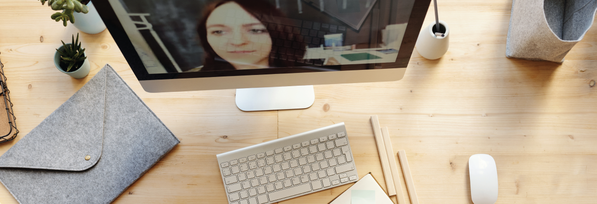Overhead view of someone at a desk who is writing in a notepad while in an online meeting.