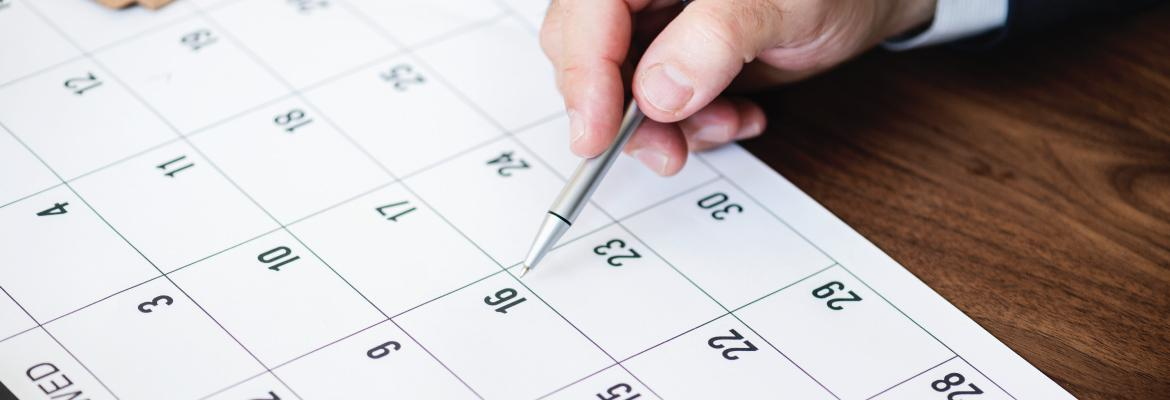 A person pointing at a calendar