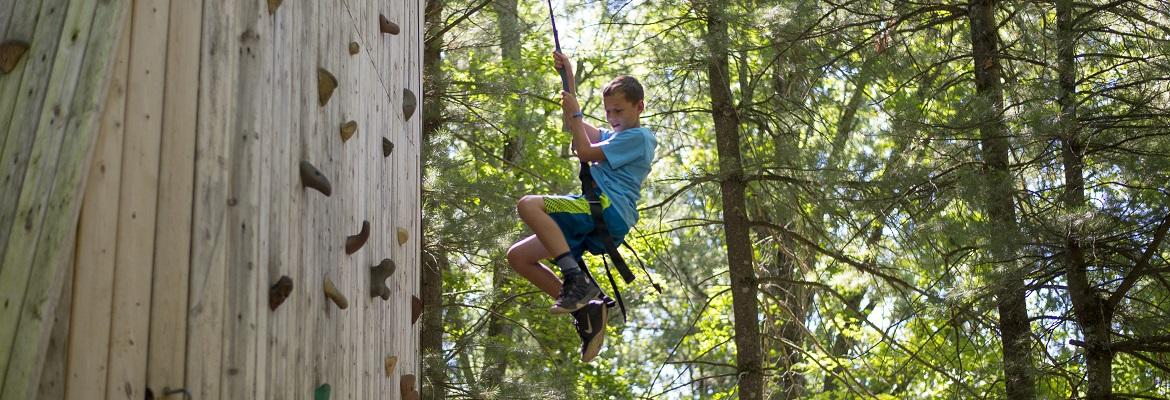 A boy smiles while rappelling down a wooden climbing wall in the woods.
