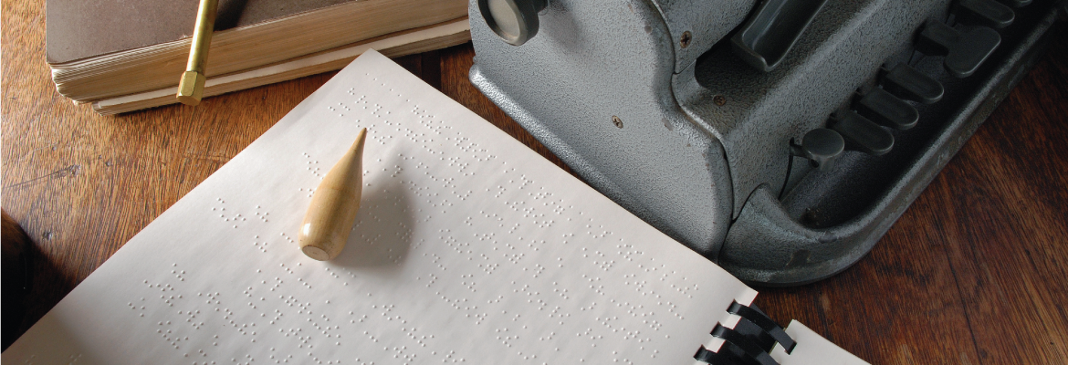 A braille writer sits on a wooden table next to a sheet of embossed braille.
