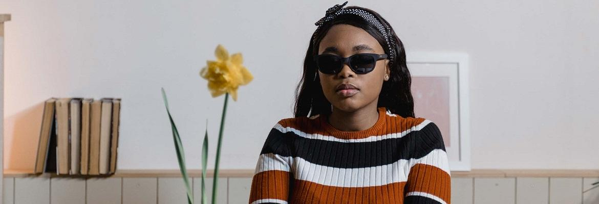A girl wearing a striped shirt and dark sunglasses stands indoors.