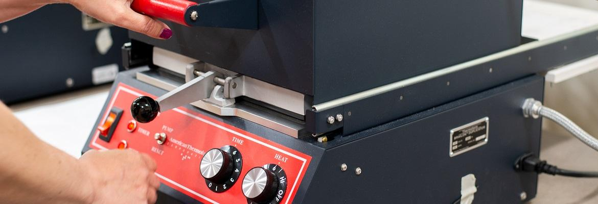 Closeup of a woman's hands pressing the top of a thermoform machine toward the base. A small red instrument panel on the front features a switch and knobs for time and heat.
