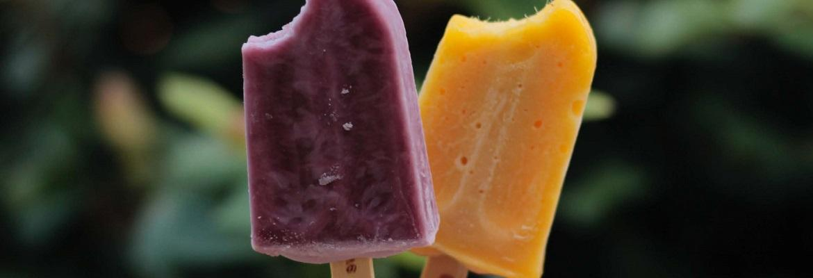 A purple popsicle and orange popsicle, with a bite taken out of each.