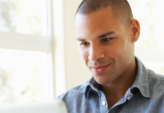 A man smiles while working at an open laptop next to a large sunny window.