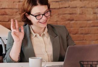 A woman sits in front of an open laptop and smiles while making a hand gesture.
