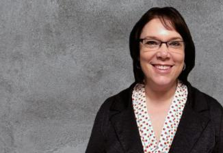 Amanda, wearing glasses, a white dotted shirt, and a black blazer, smiles for a photo in front of a gray background.