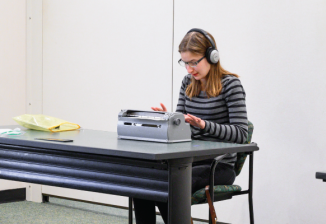 A teen girl, wearing headphones and glasses, uses a braille writer while sitting at a desk in a large room.
