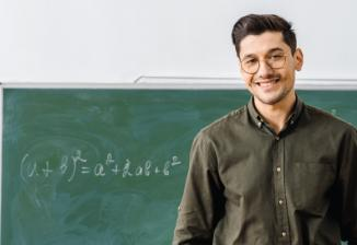 A man wearing glasses and an olive green button-down shirt smiles as he stands in front of a chalkboard with a math equation written on it.