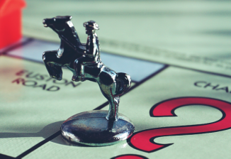 A Monopoly game piece of a horse rearing up with a rider on its back. The piece is resting on a Monopoly board.