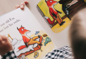 View from above of a young child reading an illustrated storybook about a fox who has lost his socks.
