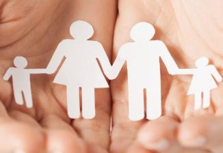 Closeup of a person's hands holding a paper stick figure cutout of a male figure and female figure holding hands with two smaller child figures.