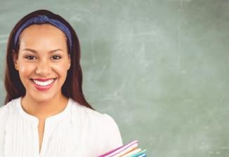 A woman with long dark brown hair and a purple headband smiles as she stands in front of a chalkboard.