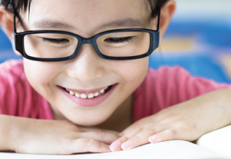 Closeup of a boy wearing glasses who is reading a book.