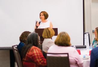 A woman with short brown hair talks into a microphone at a podium in front of a white screen at the 2018 MAER Conference.