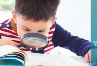 A boy with a magnifying glass reading a book