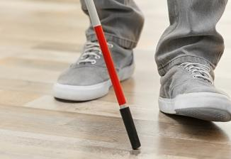Closeup of a person's shoes as they walk with a white cane.