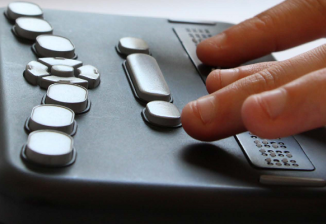Closeup of fingers touching the braille display of a black rectangular Orbit Reader.