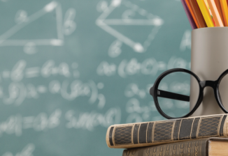 A mug and glasses rest on top of two books in front of a chalkboard.